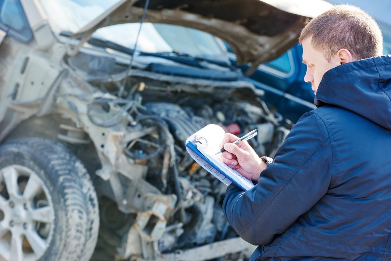 Страховой агент фиксирует повреждения автомобиля после ДТП